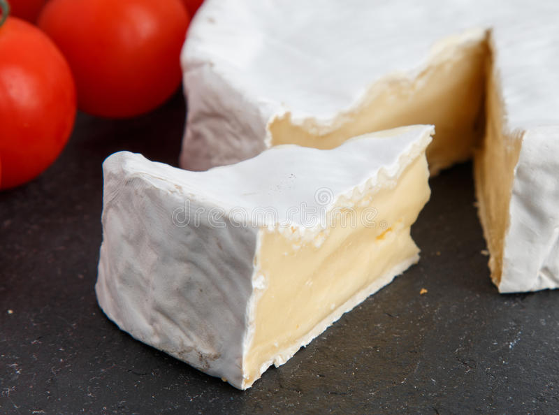 Brie soft cheese with tomato on a grey slate board. stock image