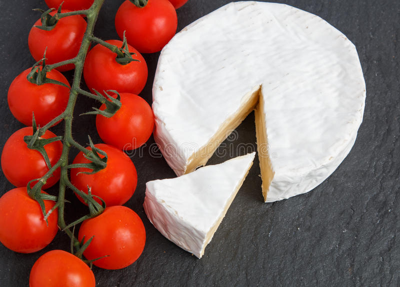 Brie soft cheese with tomato on a grey slate board. royalty free stock photo
