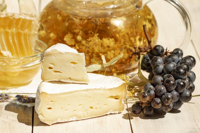 Brie type of cheese. Camembert cheese. Close up. Fresh Brie cheese and a slice on a wooden white table with honey, black stock photos
