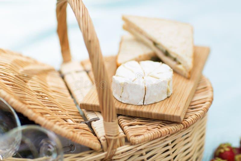 Brie und Sandwiche auf Weidenpicknickkorb stockfotos