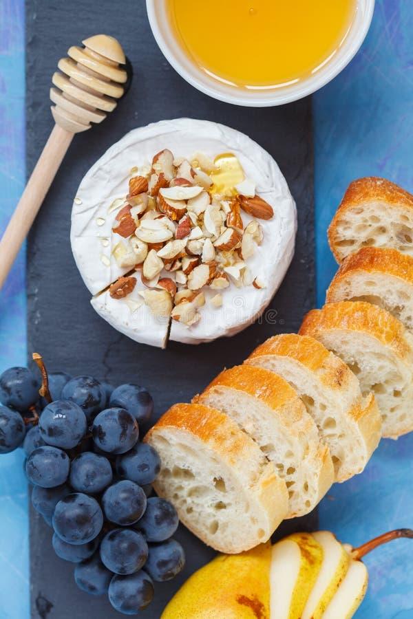 Briecamembert mit Honig, Nüssen, Stangenbrot und Frucht an stockbilder