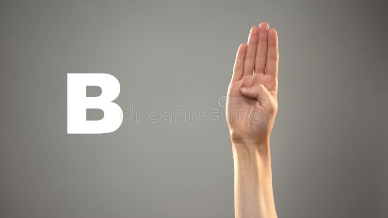 Brief B in gebarentaal, hand op achtergrond, mededeling voor doof, les stock afbeelding
