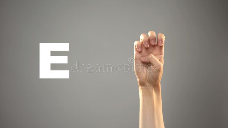 Brief E in gebarentaal, hand op achtergrond, mededeling voor doof, les royalty-vrije stock afbeeldingen