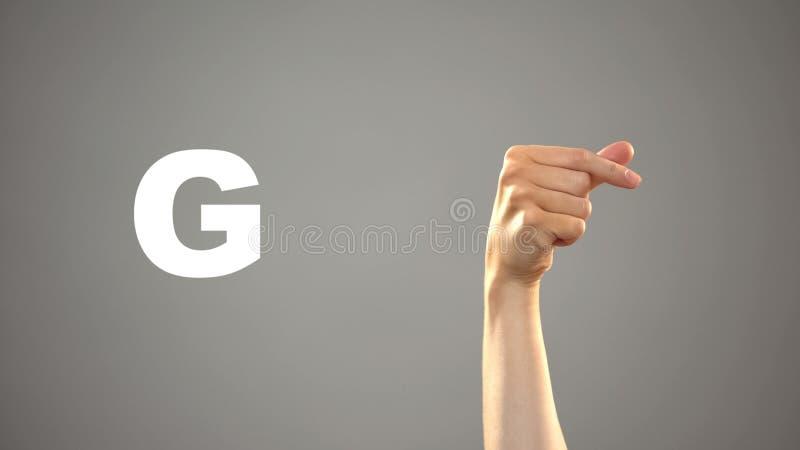 Brief G in gebarentaal, hand op achtergrond, mededeling voor doof, les stock foto