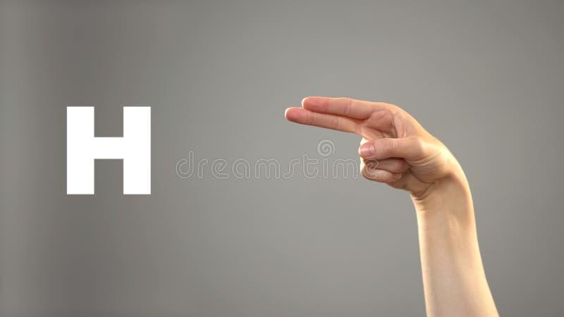 Brief H in gebarentaal, hand op achtergrond, mededeling voor doof, les stock foto's