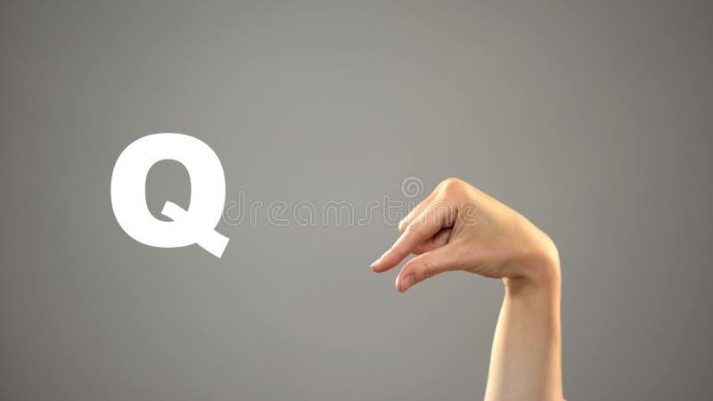Brief Q in gebarentaal, hand op achtergrond, mededeling voor doof, les stock afbeeldingen