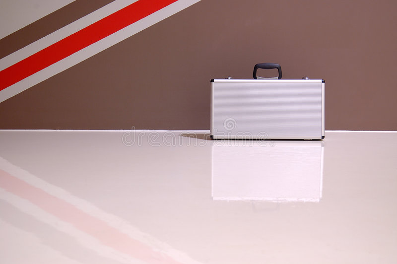 Briefcase. View of a lonely briefcase by the wall. Showing more of the floor here for your creative uses stock image