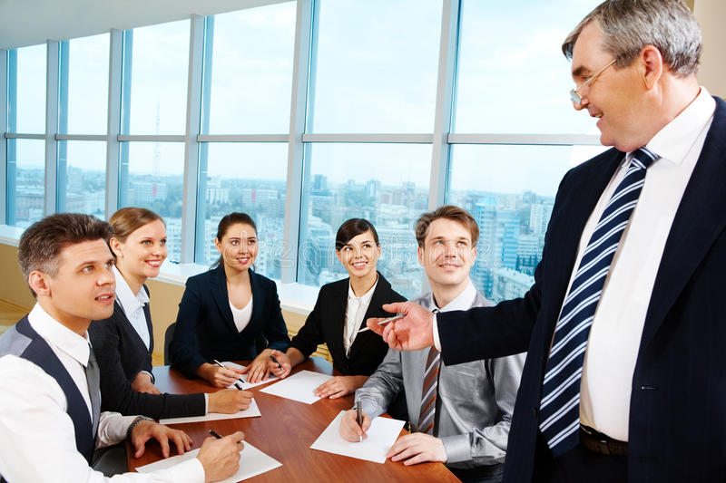 Briefing. Smart and confident boss looking at managers with papers at meeting stock photo