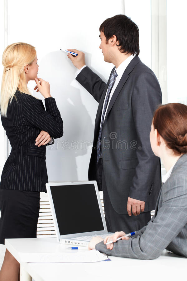 Briefing. A business man drawing a plan on a whiteboard for his colleague royalty free stock image