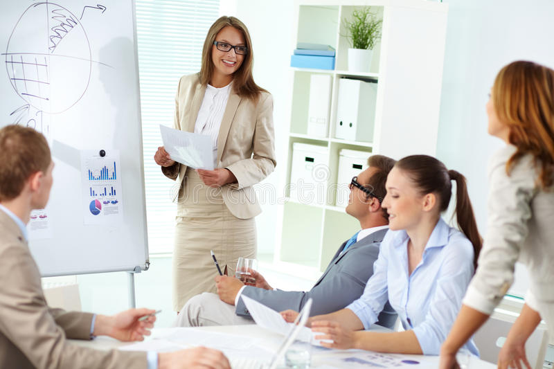 At briefing. Confident top manager standing by the whiteboard and making report at meeting stock photography