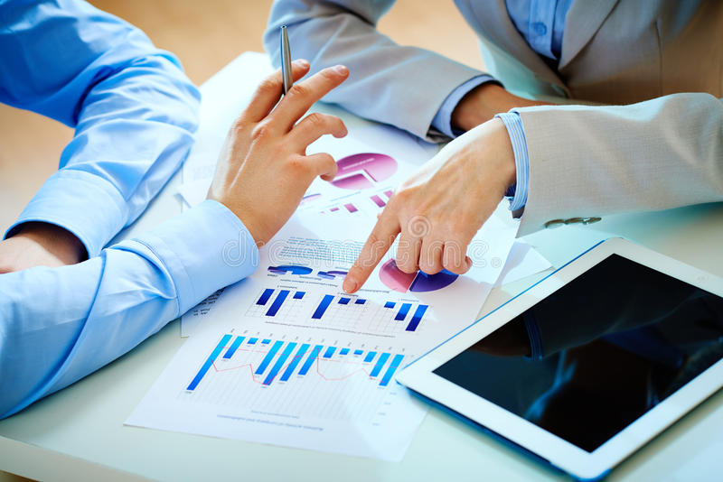 Briefing. Close-up of female hand pointing at business document while explaining chart stock image