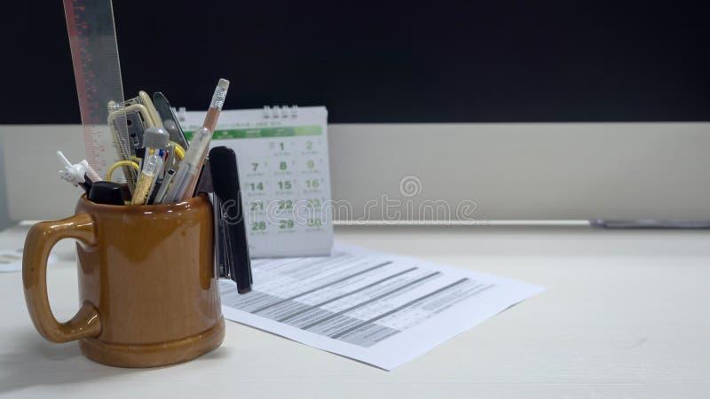 Briefpapier in einem Glas Trinkwasser auf dem Desktop lizenzfreie stockfotografie