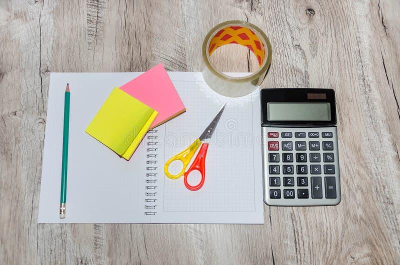 Briefpapier: Scheren, Band, Stift, Taschenrechner, Bleistift und Notizbuch auf einem Holztisch lizenzfreies stockfoto