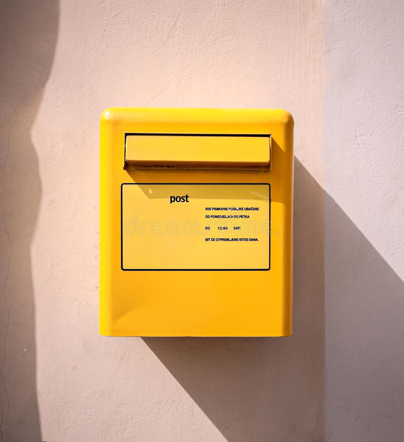 Briefpostbeitrags-Gelbkasten an der Wand stockbild