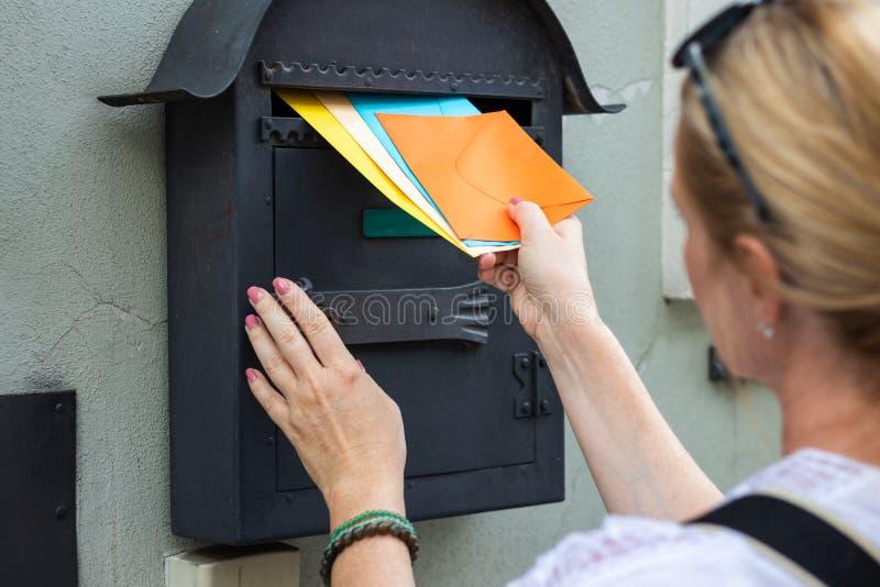 Briefträger fügt Buchstaben in Briefkasten ein lizenzfreies stockfoto