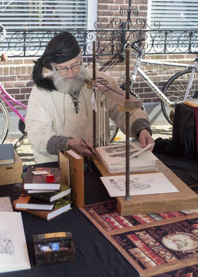 Hombre ocupado con el viejo encuadernador del hadcraft imagen de archivo