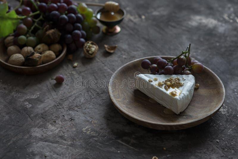 Brieostmassa med honung, valnötter och druvor royaltyfria foton