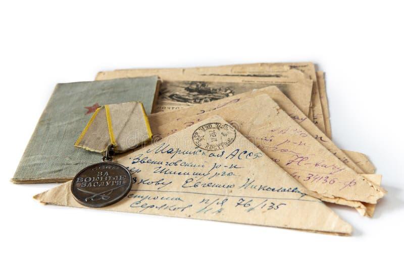 Brieven van de voorzijde van de Grote Patriottische Oorlog Het boek, de orde, en de brief-driehoeken van de militair op een wit g royalty-vrije stock fotografie