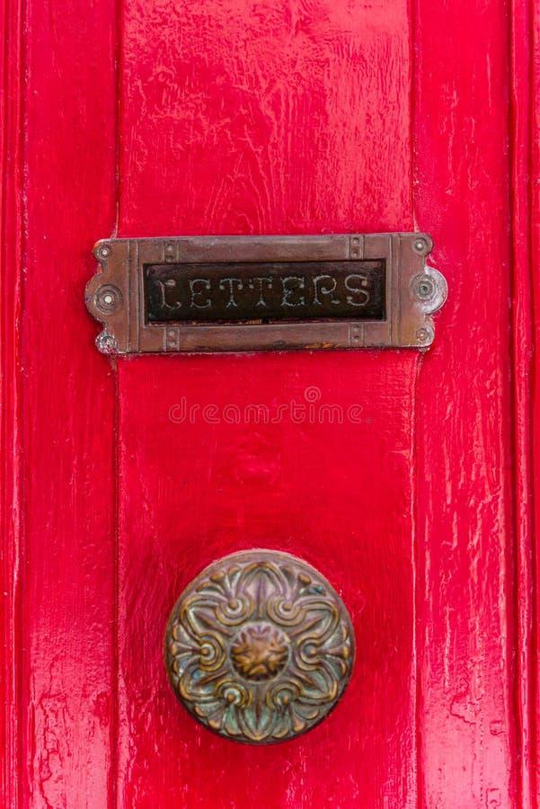 Brievenbus op de rode deur met een oud handvat royalty-vrije stock afbeelding