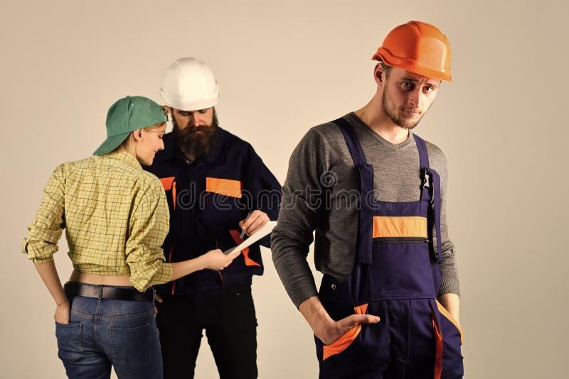 Brigada de trabajadores, de constructores en cascos, de reparadores y de señora que discuten el contrato, fondo gris Concepto del foto de archivo