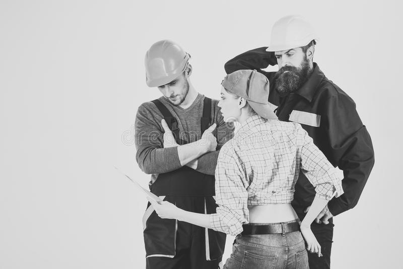 Brigade of builders. Misunderstanding between client and worker. Young Housewife Woman Arguing With Male Plumbers stock image