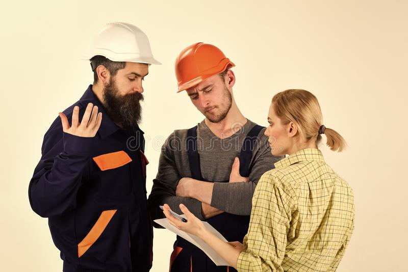 Woman amend plan of repair. Supervisor not satisfied with renovation. Brigade of workers, builders in helmets, repairers royalty free stock photos