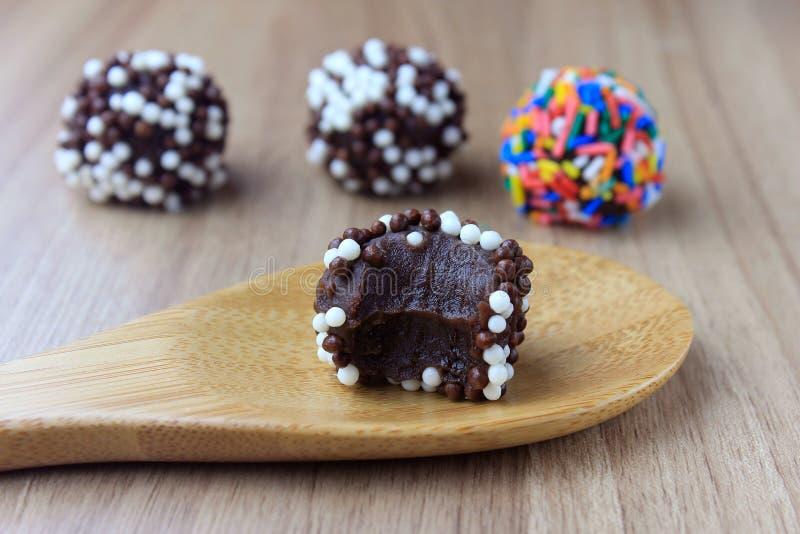 Brigadeiro brygadzista, słodka czekolada typowa Brazylijska kuchnia zakrywająca z cząsteczkami, w drewnianym tle zdjęcia royalty free