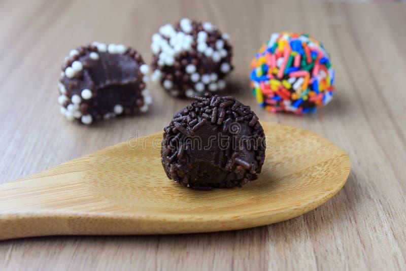 Brigadeiro brygadzista, słodka czekolada typowa Brazylijska kuchnia zakrywająca z cząsteczkami, w drewnianym tle obrazy stock