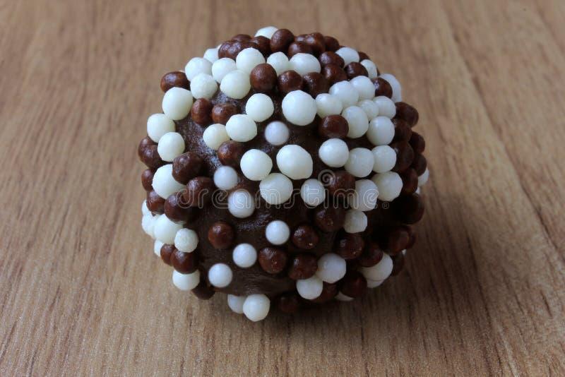 Brigadeiro brygadzista, słodka czekolada typowa Brazylijska kuchnia zakrywająca z cząsteczkami, w drewnianym tle fotografia royalty free
