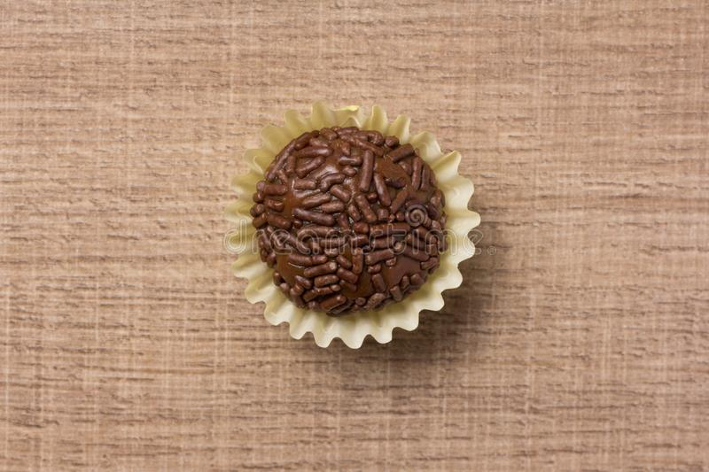 Brigadeiro is a chocolate truffle from Brazil. Cocoa and sprinkles of chocolate. Children birthday party sweet. Flat lay design o. Brigadeiro is a typical stock images