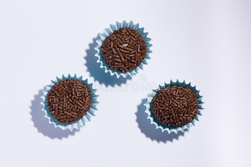 Brigadeiro is a chocolate truffle from Brazil. Cocoa and sprinkles of chocolate. Children birthday party sweet. Flat lay design o. Brigadeiro is a typical stock image