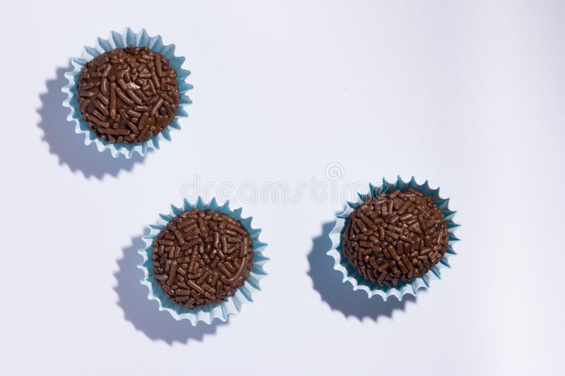 Brigadeiro is a chocolate truffle from Brazil. Cocoa and sprinkles of chocolate. Children birthday party sweet. Flat lay design o. Brigadeiro is a typical royalty free stock image