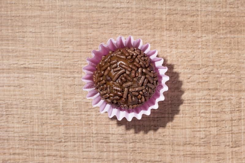 Brigadeiro is a chocolate truffle from Brazil. Cocoa and sprinkles of chocolate. Children birthday party sweet. Flat lay design o. Brigadeiro is a typical stock photo