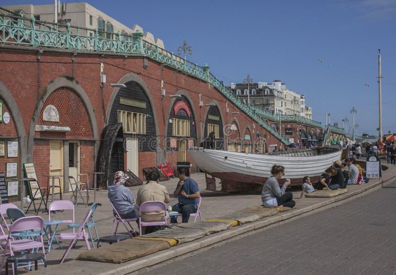 Brigghton - frente marítima em um dia ensolarado; povos e barcos imagem de stock
