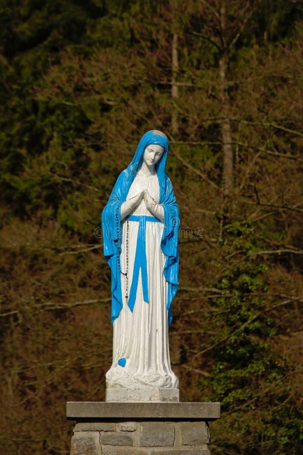 Brigh blå och vit staty av att be för dam Mary royaltyfri bild