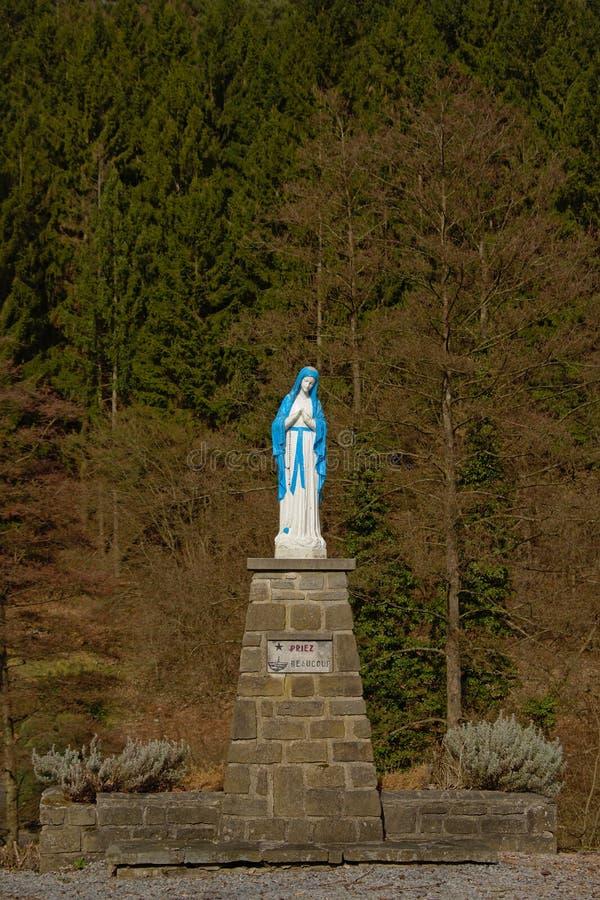 Brigh blauw en wit standbeeld van Dame Mary die op een baksteenvoetstuk bidden royalty-vrije stock foto