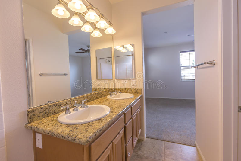 Bright apartment master bedroom bathroom with granite counter and double sinks in san diego california real estate shoot. Model homes always show off beautiful royalty free stock photos