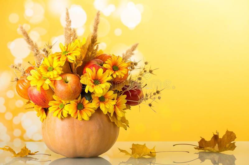 Bright autumn bouquet in a pumpkin on yellow royalty free stock photo