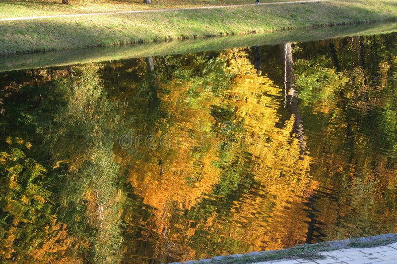 Bright autumn landscape - red, yellow and green trees on the shore of the lake are reflected in the water. Abstract autumnal background. Colorful autumn. Sunny stock photo