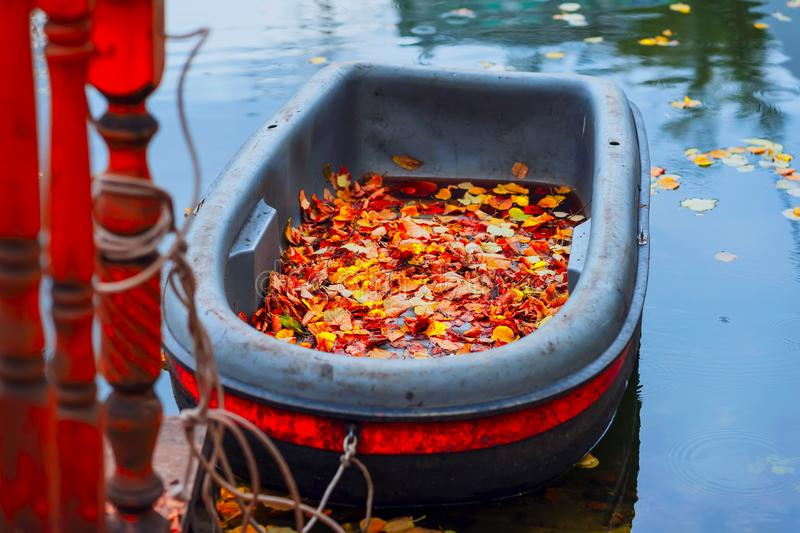 Bright Autumn scene, dirty boat in the autumn pond, fallen vivid leaves on the shore, picturesque colors of nature. Romantic seasonal mood, concept of stock image