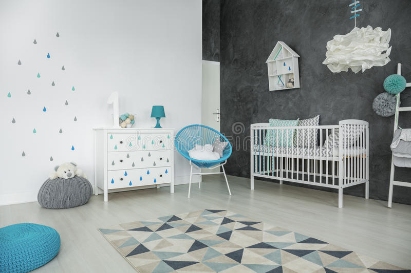 Bright baby bedroom with cot. Dresser and blue chair stock photography