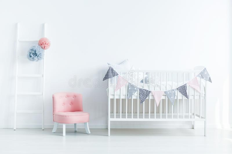 Bright baby room interior with a crib decorated with triangles o royalty free stock photography