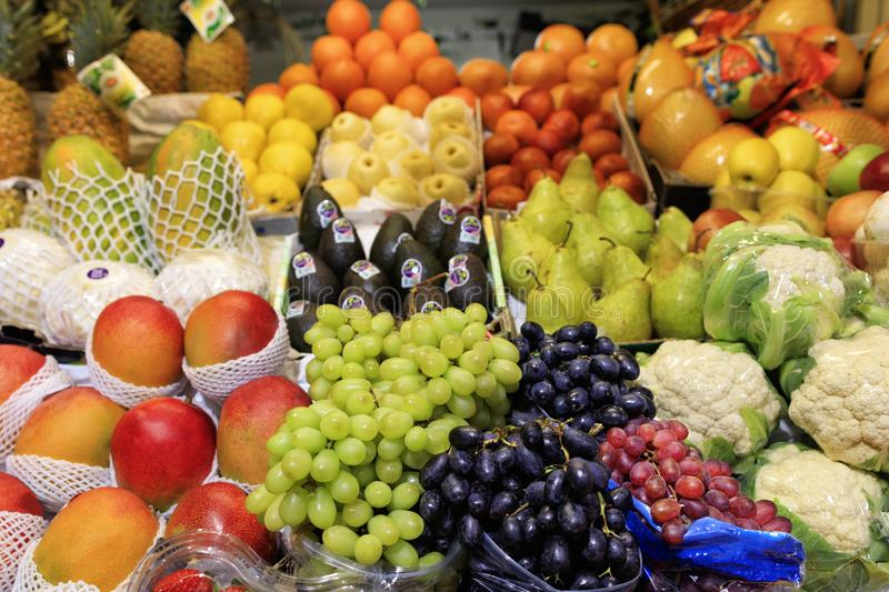 Green black red berries of grapes, mango, pears, apples, pineapple, melon are on the market for sale stock photo