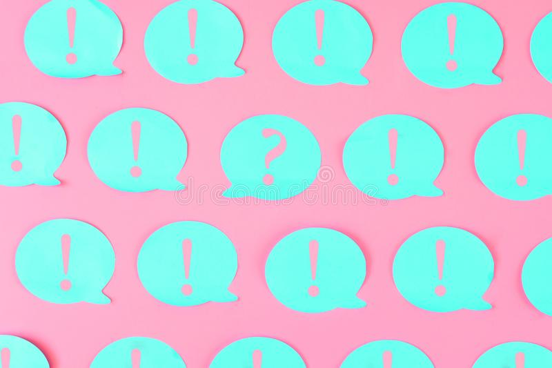 On a bright background are glued blue stickers with pink exclamation marks. In the center is a sticker with a question stock image