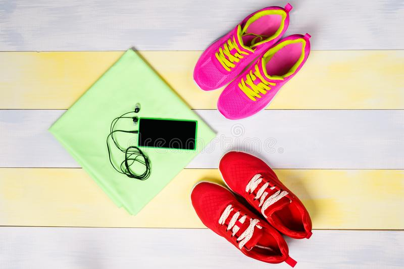 Bright background for jogging, with two pairs of shoes and a music phone stock photos