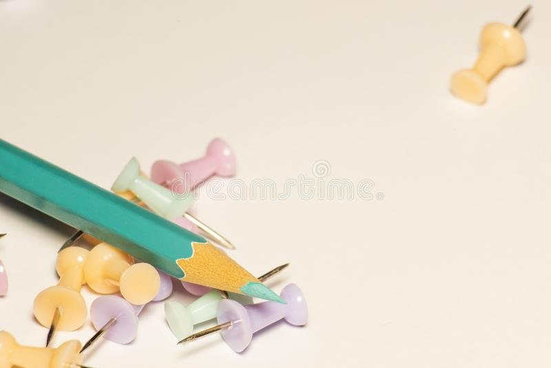 Bright background with pencil and push pins in delicate colors royalty free stock image