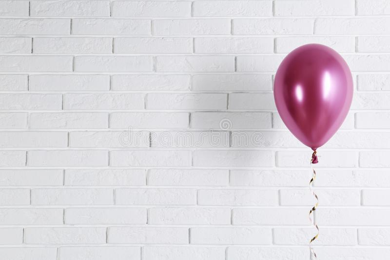 Bright balloon near brick wall, space for text. Party time stock images