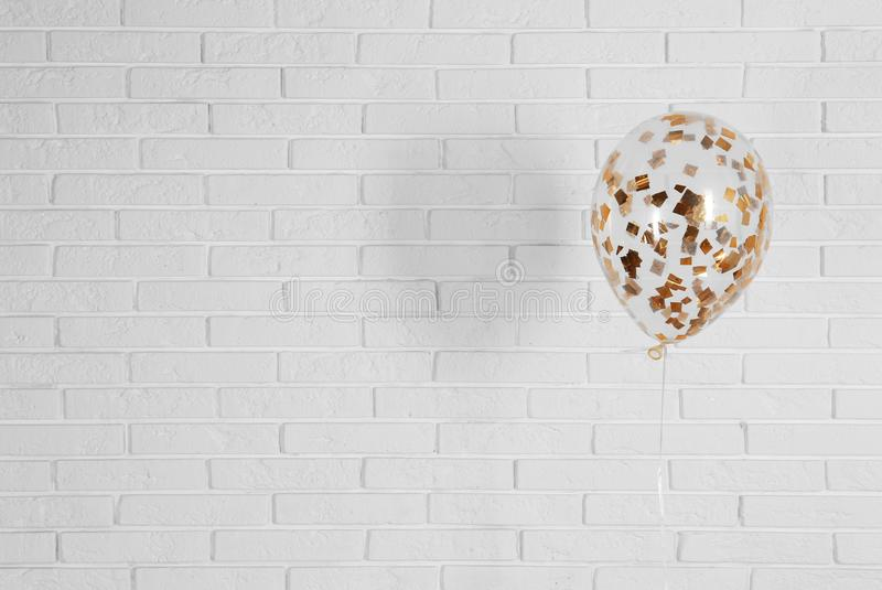Bright balloon near brick wall, space for text. Party time stock photography