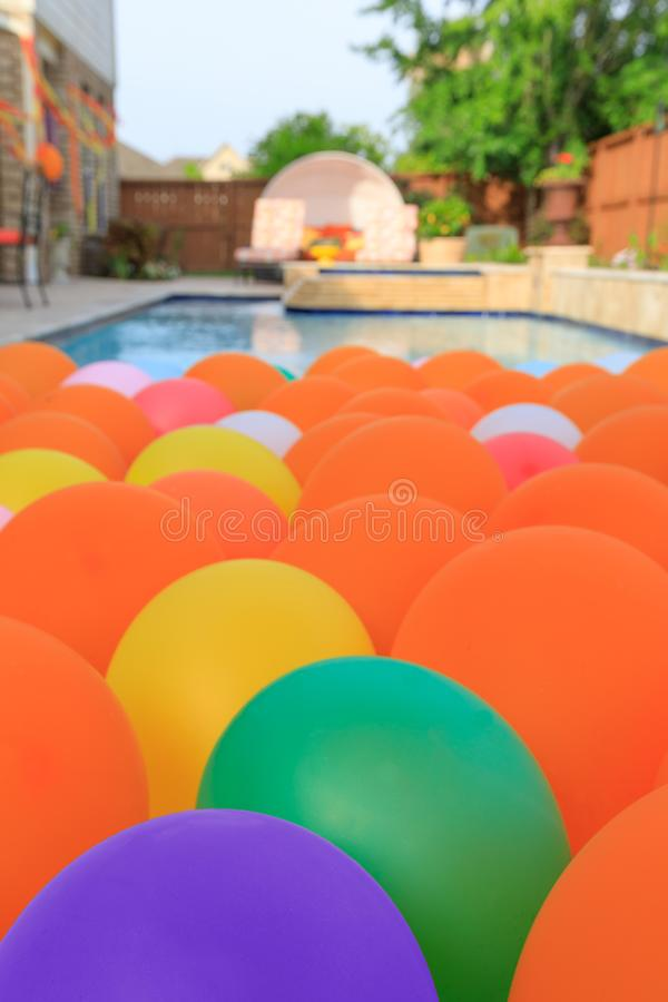 Bright balloons floating in backyard oasis royalty free stock photo