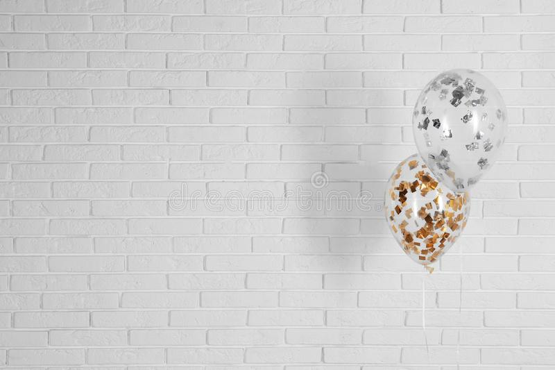 Bright balloons near brick wall, space for text. Party time royalty free stock images